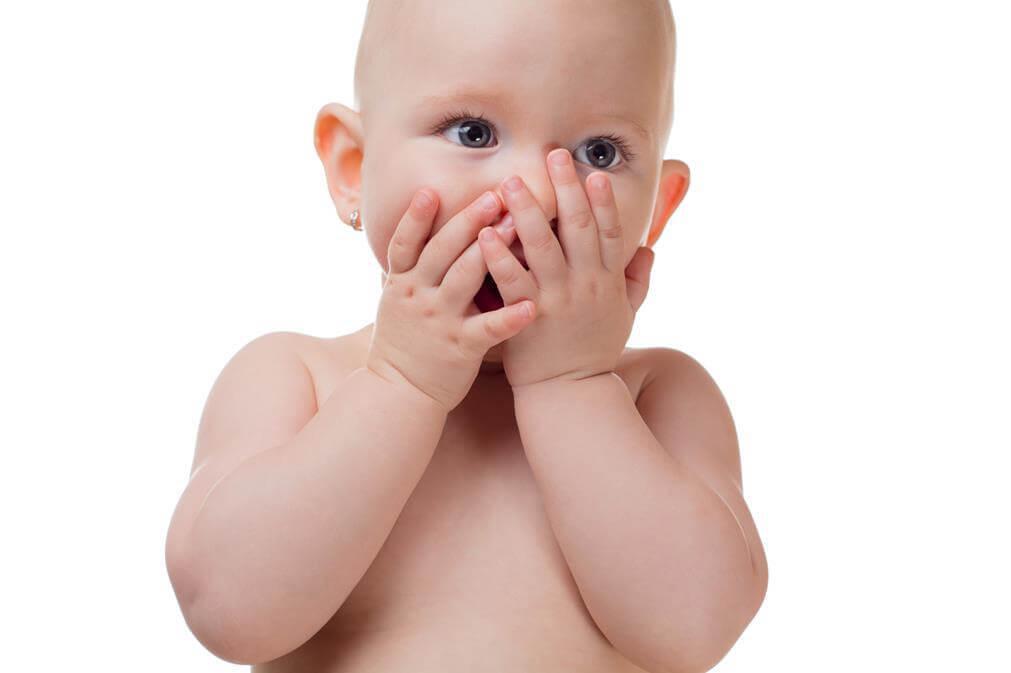 Bebé con las manos en la cara